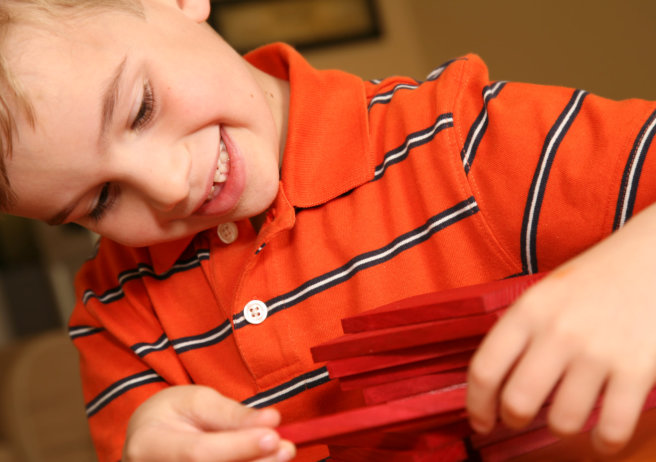 Happy Preschool boy building with red blocks
